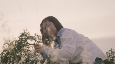 nagyító : Closeup asian young girl using magnifying glass look floral field