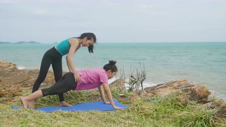 visszavonulás : Asian woman training young girl practicing yoga on mountain background sky and ocean, Healthy active lifestyle concept