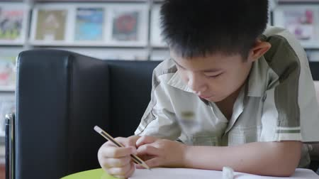 campus universitario : Asian little boy learning holding pencil working on book in library Archivo de Video