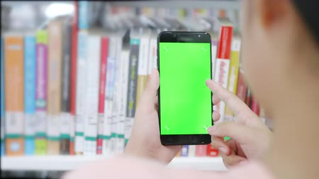 книжный магазин : Close up hand young girl holding smart phone green screen searching in libraly Стоковые видеозаписи