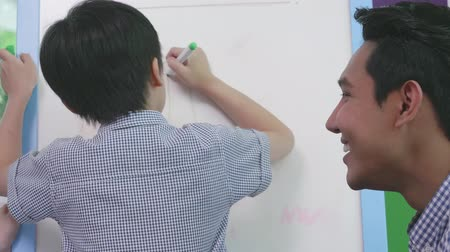 liste : Asian family parent teaching her boy try to learn writing on board in living room