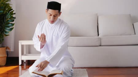 hacı : Muslim man sitting reads a koran indoors at home