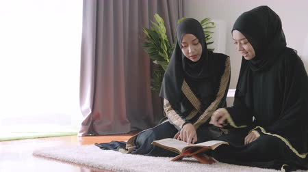 holy book : Asian muslim young woman sitting reads a koran indoors at home