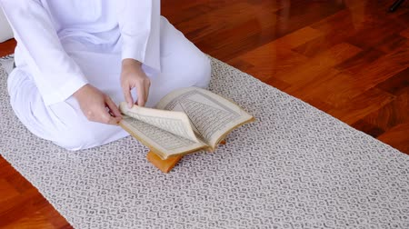 holy book : Muslim man sitting reads a koran indoors at home