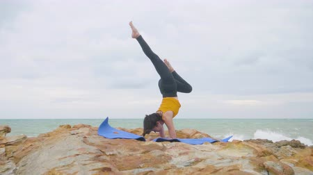 tartmak : Asian woman with a slender practicing yoga on mountain background sky and ocean, Healthy active lifestyle concept