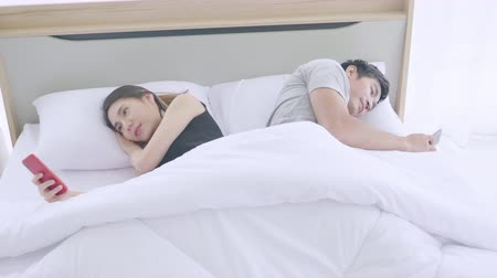 juntar : Asian couple use smart phone on bed in bedroom, Lifestyle technology concept