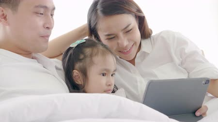 szórakoztatás : Asian family laughing and looking in digital tablet while lying on bed in bedroom,Learning via social media,Daughter looking tablet computer bright smile and laugh