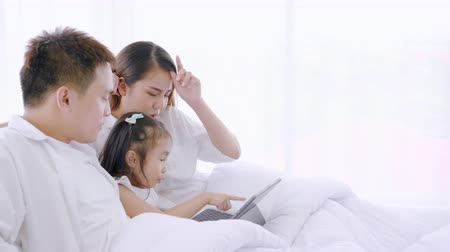 szórakoztatás : Asian family laughing and looking in digital tablet while lying on bed in bedroom, Learning via social media, Daughter looking tablet computer bright smile and laugh