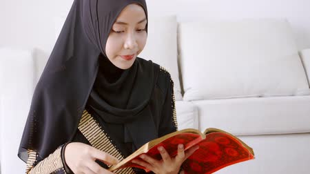 hacı : Asian muslim young woman sitting reads a koran indoors at home
