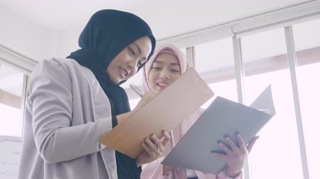dosya : Asian muslim business women stand talking in office room Stok Video