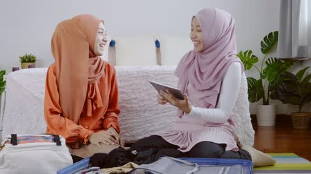 handbag : Asian muslim women packing the travel bag on the weekend, Muslim girls use a tablet to search for tourist attractions and accommodations