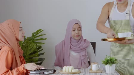 pastelaria : two muslim women sitting in coffee shop, Waiter serving coffee and cakes, Lifestyle people in restaurant Stock Footage