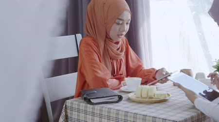 pastelaria : Two muslim women holding playing phone in restaurant, Society people concept, Lifestyle people in restaurant