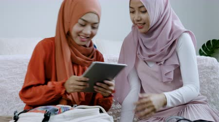 tasje : Asian muslim women packing the travel bag on the weekend,Muslim girls use a tablet to search for tourist attractions and accommodations Stockvideo