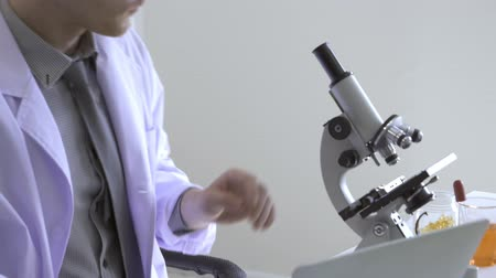 vzorec : Scientists doing research in the science room, Man Scientists use microscope in lap Dostupné videozáznamy