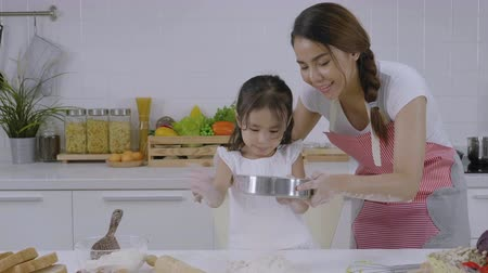 blending : Asian family, Mother who are teaching their daughter to learn to make bread, Daughter is having fun playing the dough Stock Footage