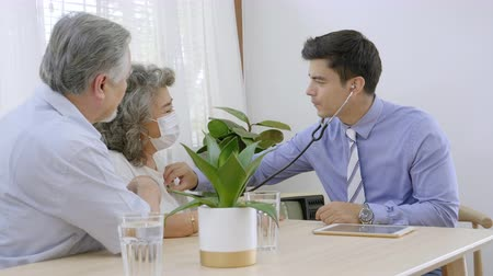 poptávka : Health doctor visitor elderly couple during home visit,doctor men checking examining a grandmother