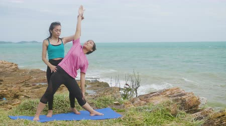 tartmak : Asian woman training young girl practicing yoga on mountain background sky and ocean, Healthy active lifestyle concept