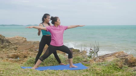 Asian woman training young girl practicing yoga on mountain background sky and ocean, Healthy active lifestyle concept