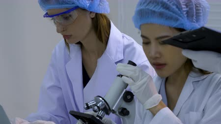 produtos químicos : Scientists doing research in the science room, Women Scientists use microscope in lap Stock Footage