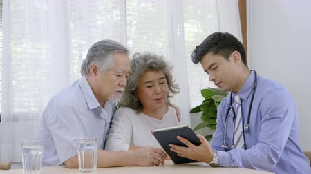 poptávka : Health doctor visitor elderly couple during home visit,doctor men checking examining a grandmother, Describe the illness on a tablet Dostupné videozáznamy