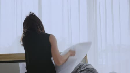 Asian couple having pillow fight on the bed, having fun and laughing