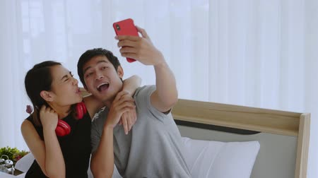 Asian women use headphones listen to music and sing karaoke in the bedroom, Man use smartphone selfie on bed