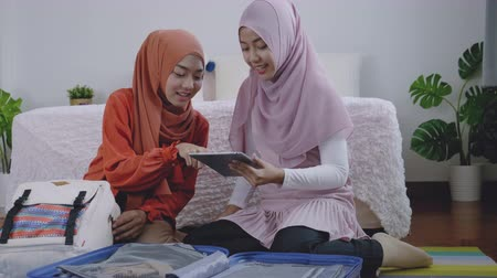 Asian muslim women packing the travel bag on the weekend,Muslim girls use a tablet to search for tourist attractions and accommodations Stok Video