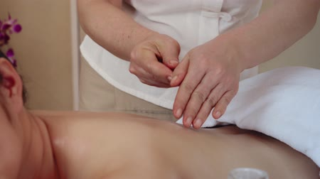 Asian woman relaxing while receiving a massage from a professional masseuse for beauty and health.Masseuse use oil massaging on body of Asian women Стоковые видеозаписи