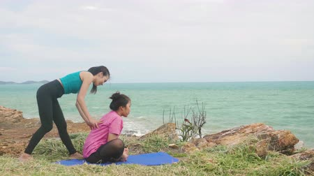 tartmak : Asian woman training young girl practicing yoga on mountain background sky and ocean,Healthy active lifestyle concept