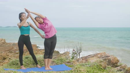 Asian woman training young girl practicing yoga on mountain background sky and ocean,Healthy active lifestyle concept