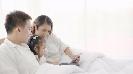 Asian family laughing and looking in digital tablet while lying on bed in bedroom,Learning via social media,Daughter looking tablet computer bright smile and laugh,Education on digital tablat Stok Video