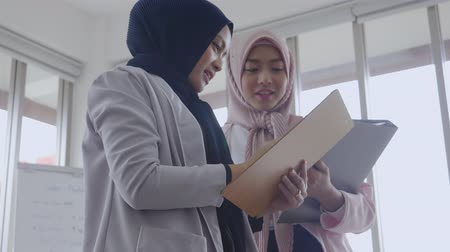 Asian muslim business women stand talking in office room Stok Video
