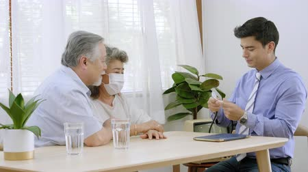 Health doctor visitor elderly couple during home visit,doctor men checking examining a grandmother,Describe the illness on a tablet