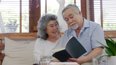 Asian elderly couple sitting reading book in the living room,Sitting and talking with a smile on the face