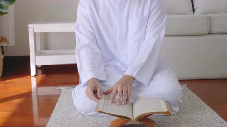 Muslim man sitting reads a koran indoors at home