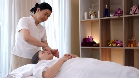 young girl relaxing while receiving a massage from a professional masseuse for beauty and health.Masseuse massaging the head and face of Asian women