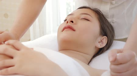 Asian woman relaxing while receiving a massage from a professional masseuse for beauty and health.Professional masseuse use herbal ball massaging on body of Asian women