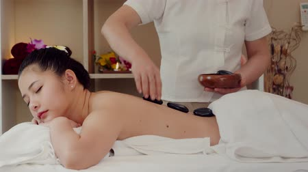 Asian woman relaxing while receiving a massage from a professional masseuse for beauty and health.Masseuse use hot stones massaging on body of Asian women