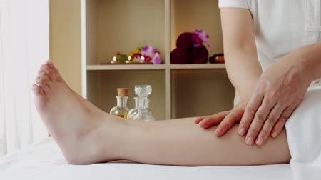 obnovitelný : Asian woman relaxing while receiving a massage from a professional masseuse for beauty and health.Masseuse who is massage the legs and arms of an Asian woman. Dostupné videozáznamy