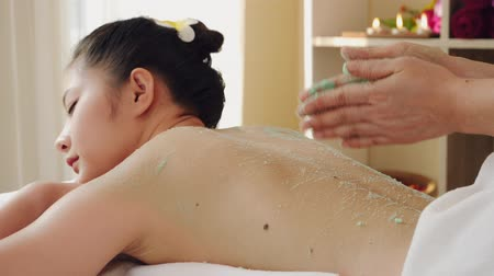 Asian woman relaxing while receiving a massage from a professional masseuse for beauty and health.Masseuse use salt massage the body of an Asian woman Stok Video