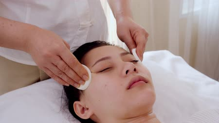 Asian women relax while receiving facial care by means of facial cleansing