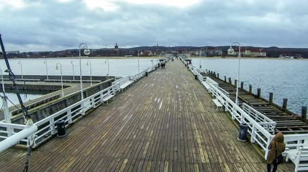túmulo : People walking on a Pier (Molo) in Sopot city, Poland. Built in 1827 with 511m long it is the longest wooden pier in Europe (Time Lapse)