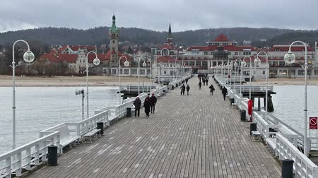 túmulo : SOPOT, POLAND - DECEMBER 12, 2017: People walking on a Pier (Molo) in Sopot city, Poland. Built in 1827 with 511m long it is the longest wooden pier in Europe