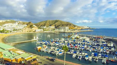 Panoramic aerial view of sea port and small bay of Puerto Rico de Gran Canaria holiday resort. Gran Canaria island, Spain. Time Lapse