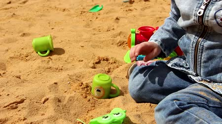 лопата : Little girl is playing in the sandbox