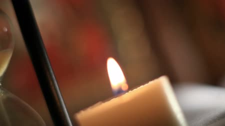time flow : Burning Candle Near A Hourglass Stock Footage