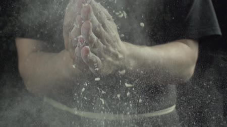 impastare : Cook claps hands with flour in the kitchen slow motion