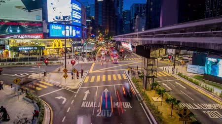 bintang : Kuala Lumpur, Malaysia - October 14 2017: Panning left view of transportation rush at night through the Bukit Bintang intersection in the Kuala Lumpur City Center Stock Footage