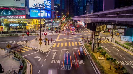 bintang : Kuala Lumpur, Malaysia - October 14 2017: Panning up view of transportation rush at night through the Bukit Bintang intersection in the Kuala Lumpur City Center